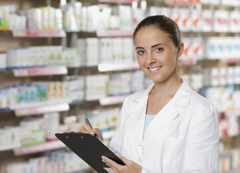 Smiling Woman Pharmacist. Environmental Portrait of a medical personnel, or doctor in pharmacy royalty free stock photography