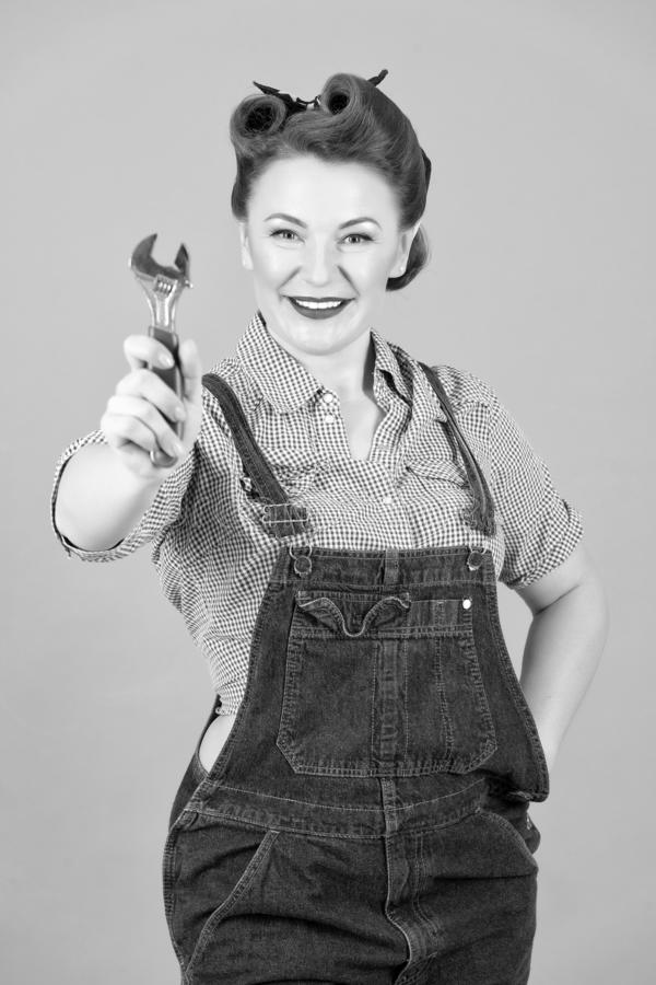 Smiling woman in pin-up style showing wrench in hand on camera. Caucasian brunette model posing in retro fashion and vintage stock images