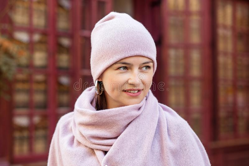 Smiling woman in a pink knitted hat and scarf. Concept lifestyle, autumn, urban.  stock image
