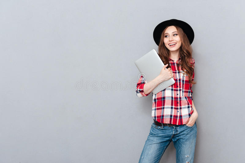 Smiling woman in plaid shirt holding laptop and looking away. Portrait of a casual smiling woman in plaid shirt holding laptop and looking away isolated over royalty free stock photography