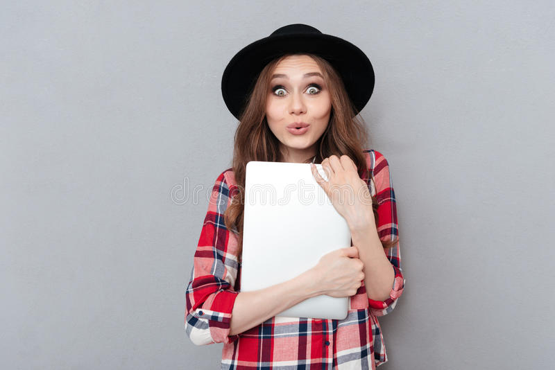 Smiling woman in plaid shirt holding laptop. Portrait of a cheerful excited woman in plaid shirt holding laptop and looking at camera isolated over gray royalty free stock image