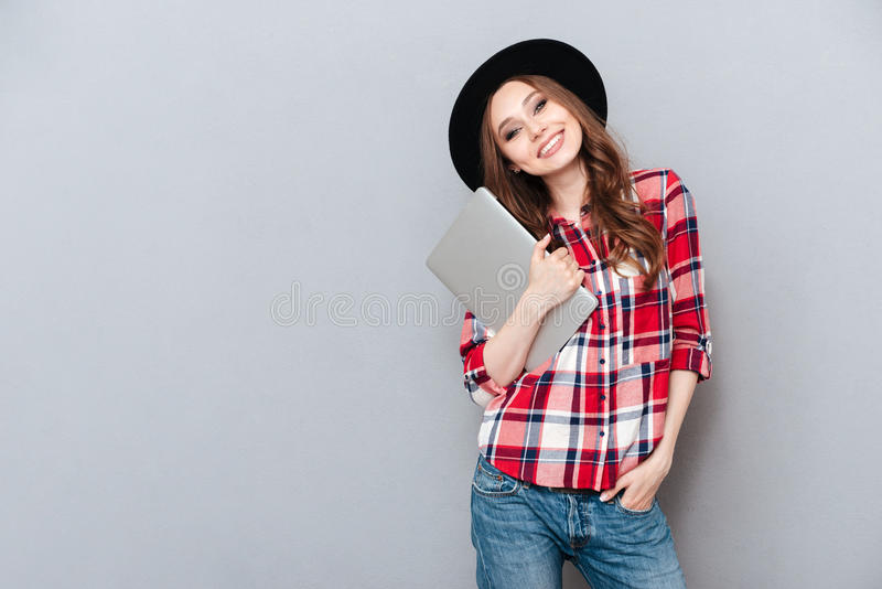 Smiling woman in plaid shirt holding laptop. Portrait of a cheerful smiling woman in plaid shirt holding laptop and looking at camera isolated over gray royalty free stock photos