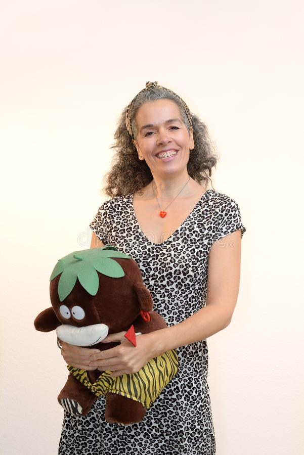 Smiling woman 50+ with plush toy Exotic animal pattern. A smiling woman with graying hair is holding a plush toy in her arms. The toy and her are dressed in stock photos