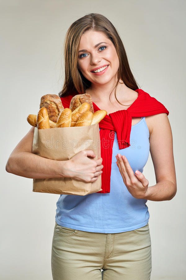 Smiling woman pointing to shopping bag with bread. stock photography