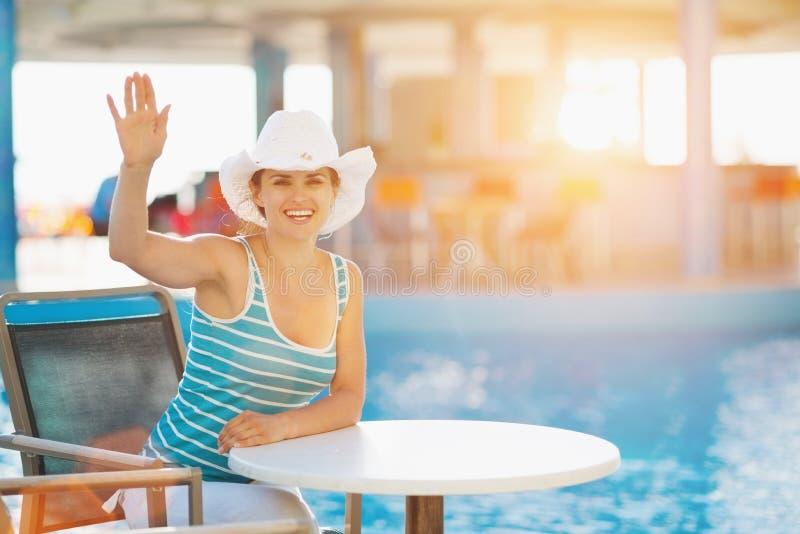 Smiling woman at pool bar saluting. Smiling young woman at pool bar saluting royalty free stock photos