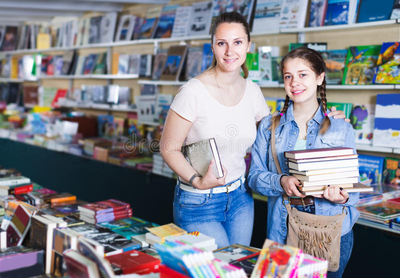 Smiling woman with positive girl taking literature books in store with prints. Smiling women with positive girl taking literature books оff the shelf in store royalty free stock photo