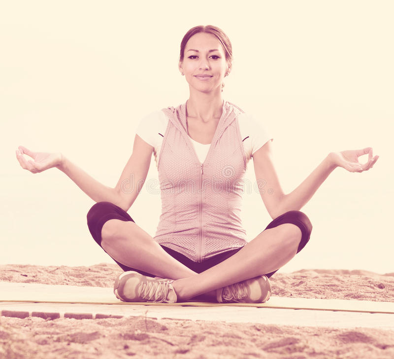 Smiling woman practise yoga cross-legged. In morning by sea royalty free stock image