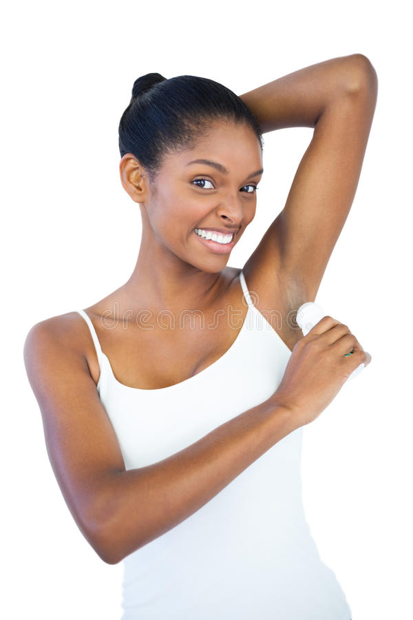 Smiling woman putting deodorant on her armpit royalty free stock images