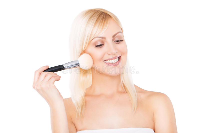 Smiling woman putting make-up on. beautiful young stock image