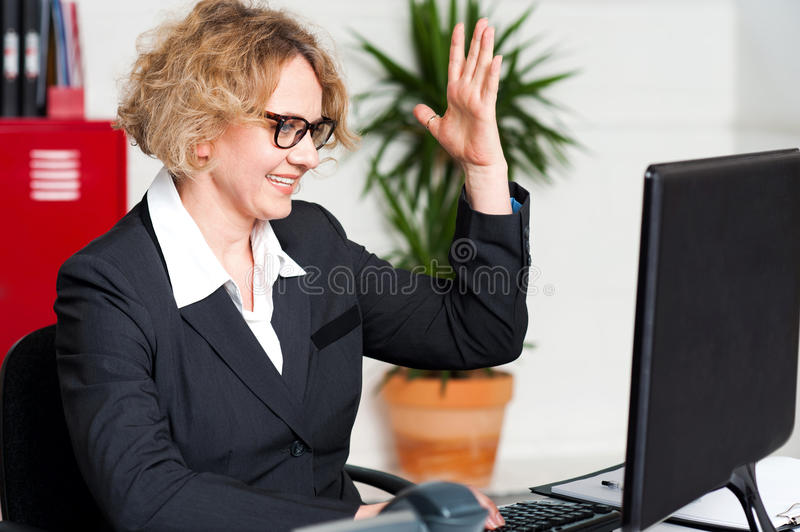 Smiling woman with raised arm looking at screen