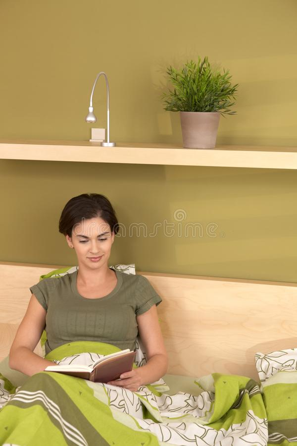 Smiling woman reading in bed royalty free stock photography