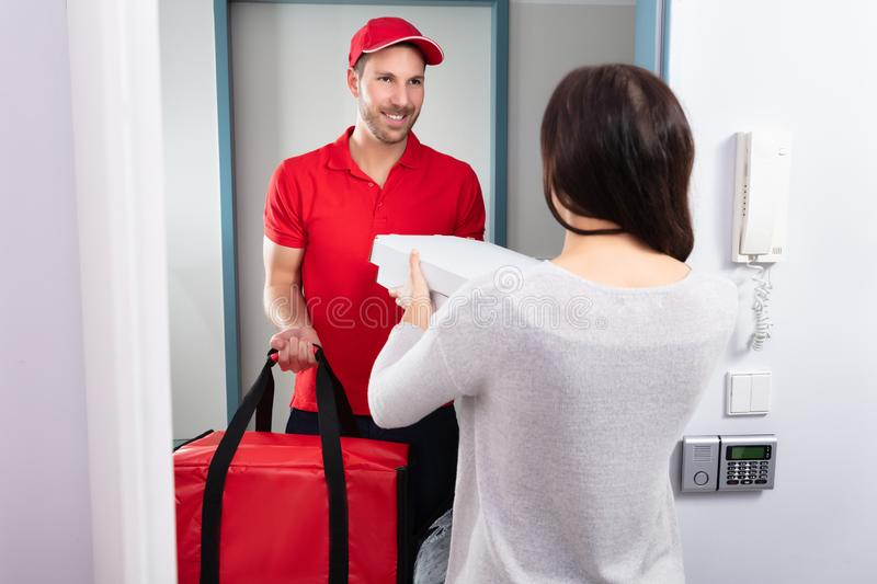 Man Delivering Pizza To Woman. Smiling Woman Receiving Pizza From Delivery Man At Home stock photography
