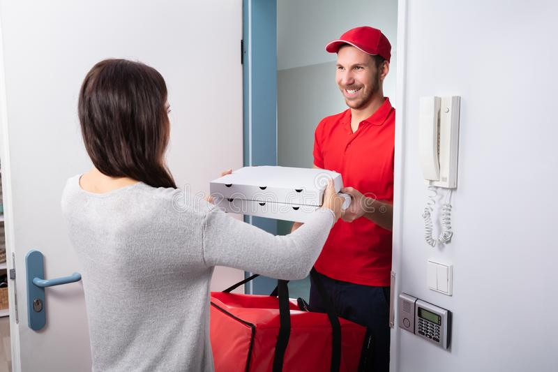 Man Delivering Pizza To Woman. Smiling Woman Receiving Pizza From Delivery Man At Home royalty free stock photo