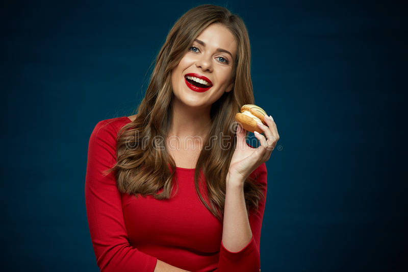 Smiling woman in red dress holding cake. royalty free stock photo