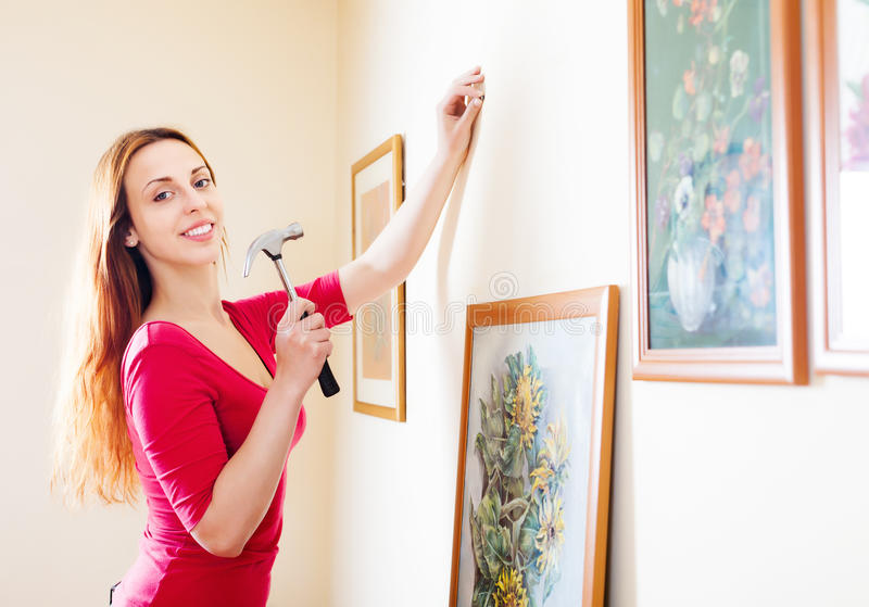Smiling woman in red hanging art picture royalty free stock images