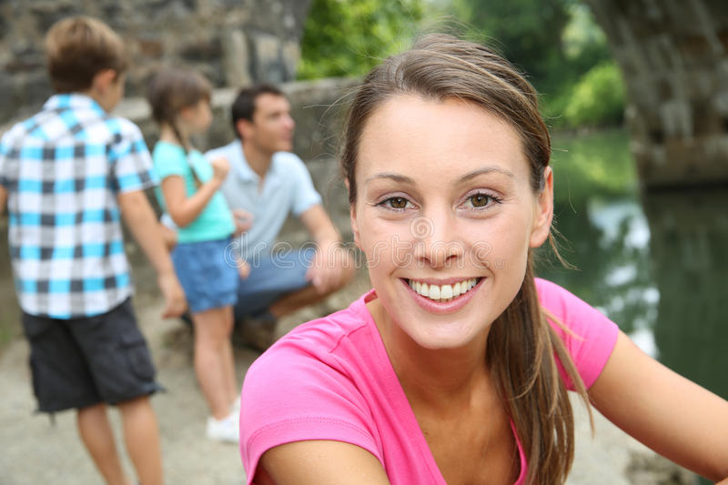 Smiling woman relaxing with family near river royalty free stock photo