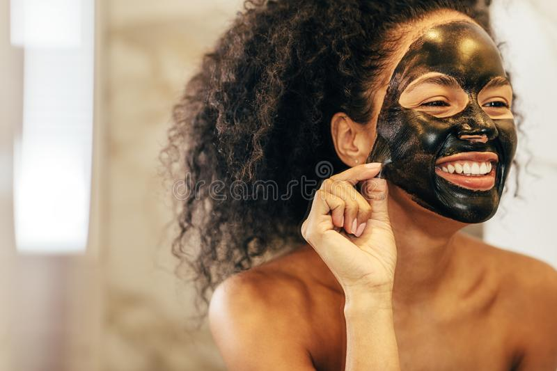 Smiling woman removing black cosmetic mask. From her face stock photo