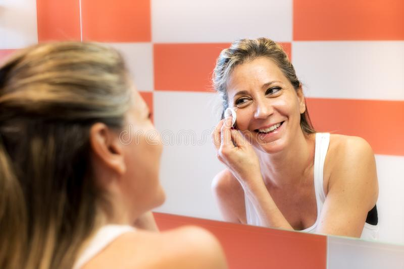 Smiling woman removing makeup royalty free stock image
