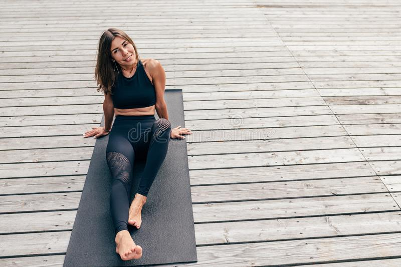 Smiling woman resting after yoga exercises stock images