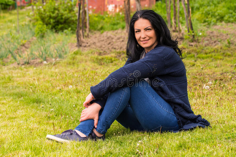 Smiling woman rests in garden. Smiling woman rests on grass in countryside garden royalty free stock photography