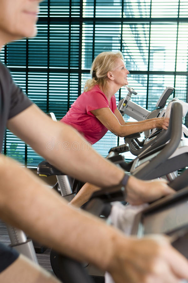 Smiling woman riding exercise bike in health club. Smiling women riding exercise bike in health club stock photos