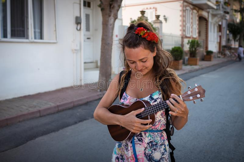 Smiling woman with roses in hairstyle holds in hands musical instrument. Pretty girl walks on the street and plays on ukulele royalty free stock photography