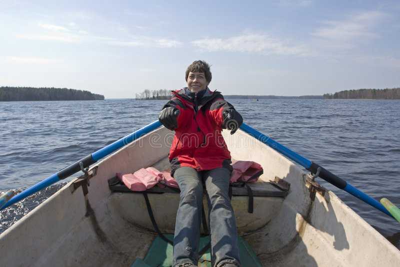 Smiling woman rowing on boat. Young smiling woman rowing on boat on a big forest lake in Karelia royalty free stock images