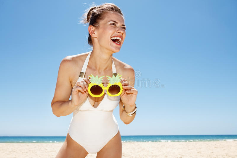 Smiling woman at sandy beach holding funky pineapple glasses stock photography