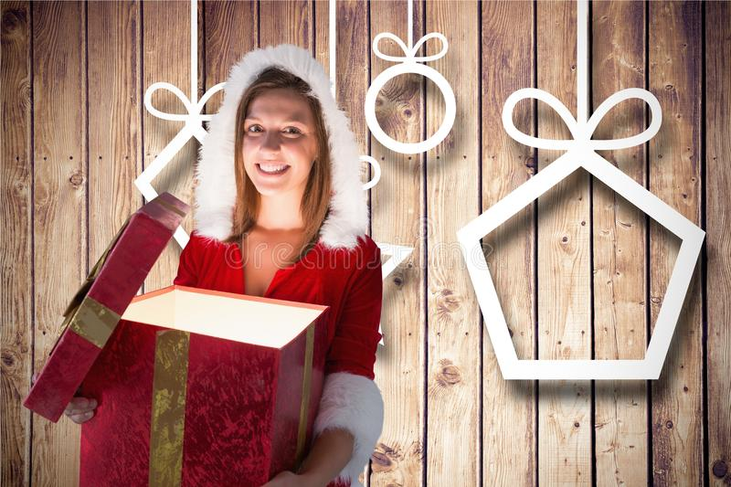Smiling woman in santa costume opening her gift box against wooden background stock photo