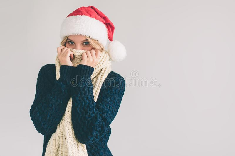 Smiling woman in Santa hat , isolated on white. The girl is dressed in sweater, christmas cap and scarf studio shot royalty free stock photos