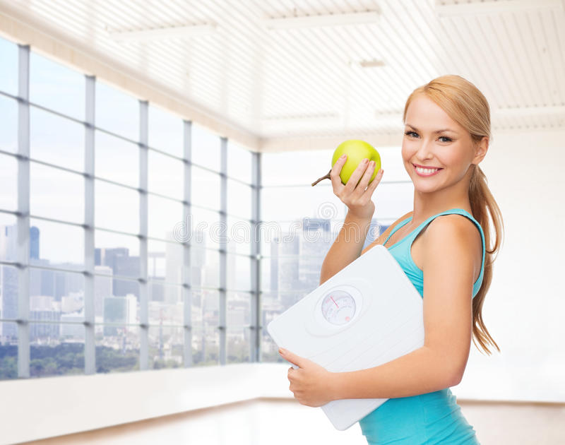 Smiling woman with scale and green apple in gym stock