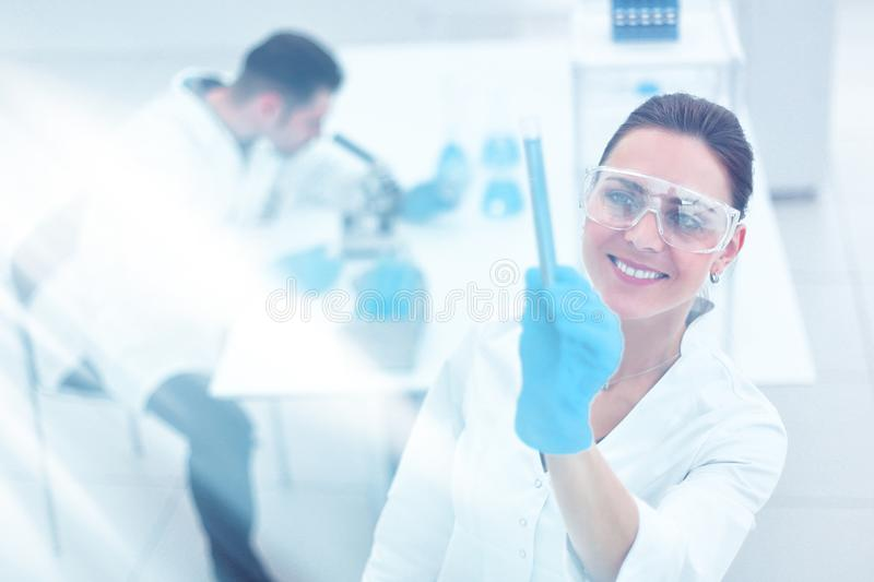 Smiling woman scientist looking at the tube with the results of the analysis royalty free stock photography