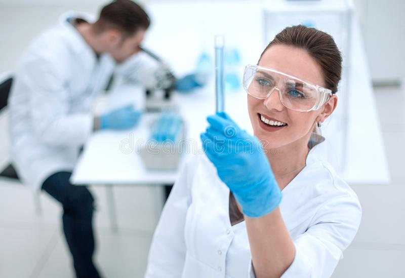 Smiling woman scientist looking at the tube with the results of the analysis stock images