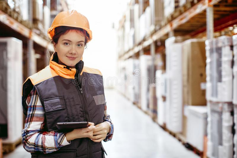 Smiling woman scrolling digital tablet warehouse stock image