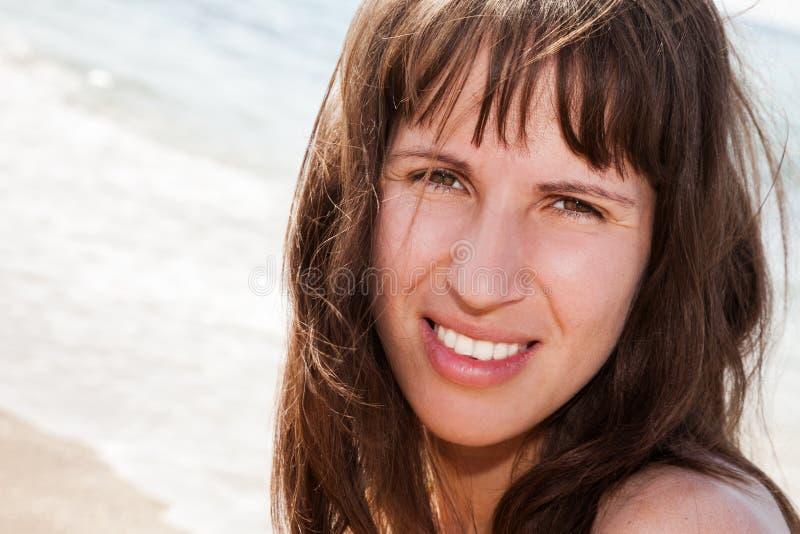 Smiling woman on sea beach