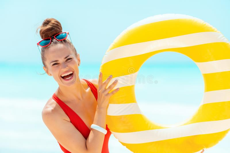 Smiling woman on seacoast showing yellow inflatable lifebuoy. Portrait of smiling modern woman in red swimwear on the seacoast showing yellow inflatable lifebuoy stock images