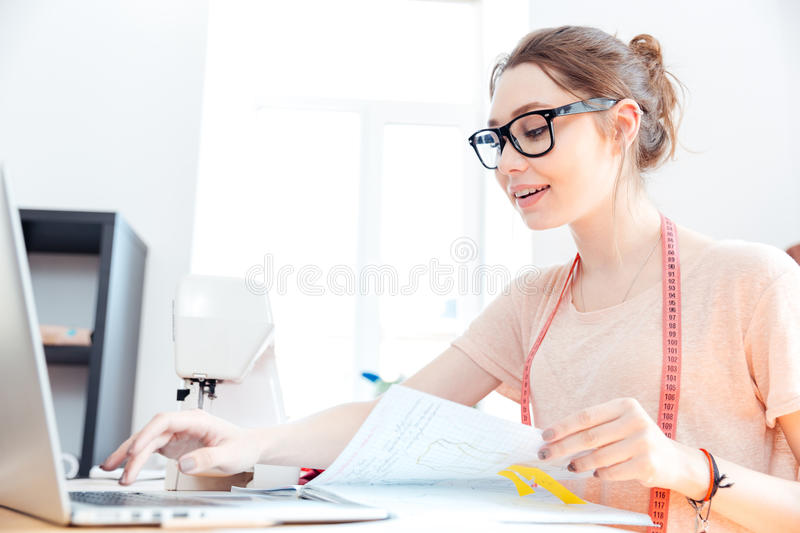 Smiling woman seamstress working with laptop in studio. Smiling charming young woman seamstress working with laptop in studio stock photography