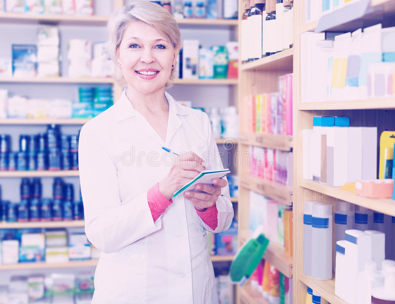 Smiling woman seller writing down care products in shop. Smiling woman seller writing down assortment of care products in shop stock photography