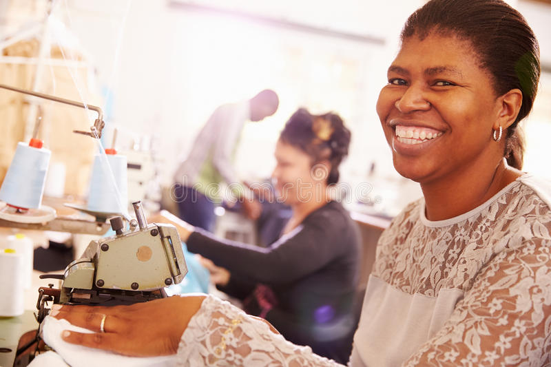 Smiling woman sewing at a community workshop, South Africa. Smiling women sewing at a community workshop, South Africa royalty free stock image