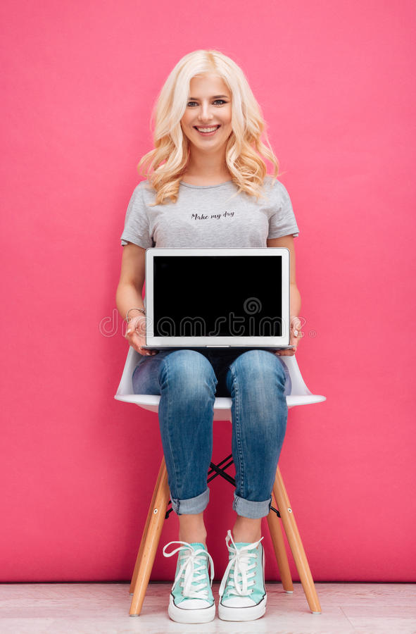 Smiling woman showing blank laptop computer screen royalty free stock photography