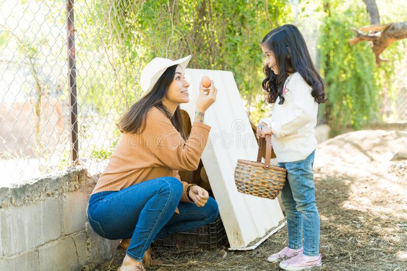 Smiling Woman Showing Egg To Little Girl At Farm royalty free stock photography