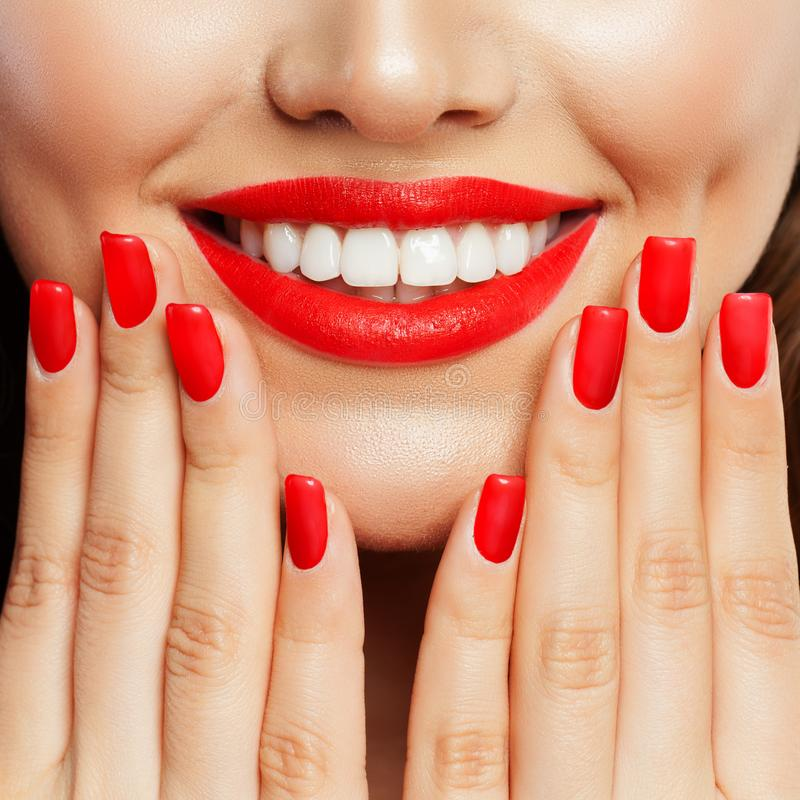 Smiling woman showing her hand with manicured nails. Red nail polish and makeup lips with bright red color tint lipstick stock images