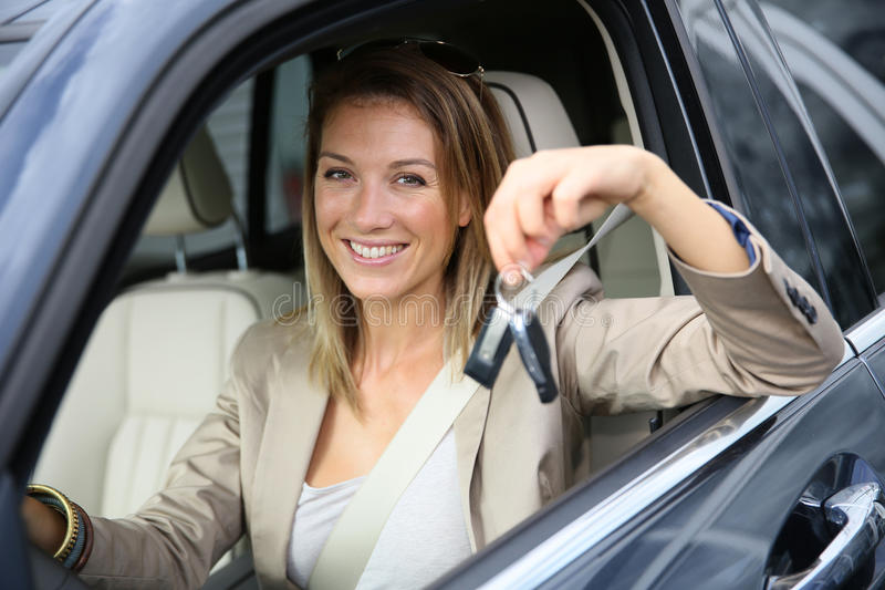 Smiling woman showing keys of recently bought car stock photography