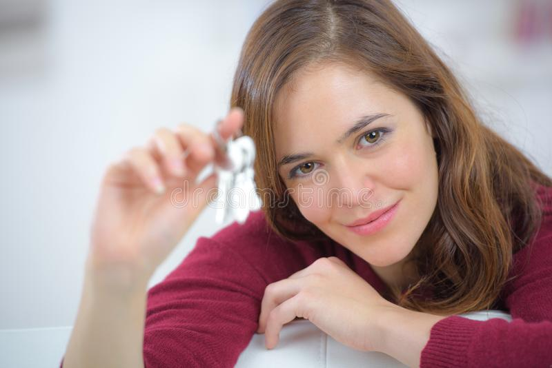 Smiling woman showing keys. Woman royalty free stock photo