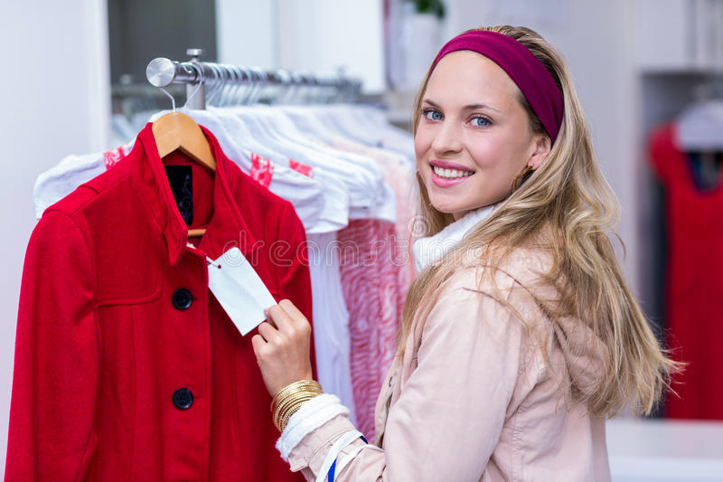 Smiling woman showing price tag to camera. Portrait of smiling woman showing price tag to camera in clothing store royalty free stock image