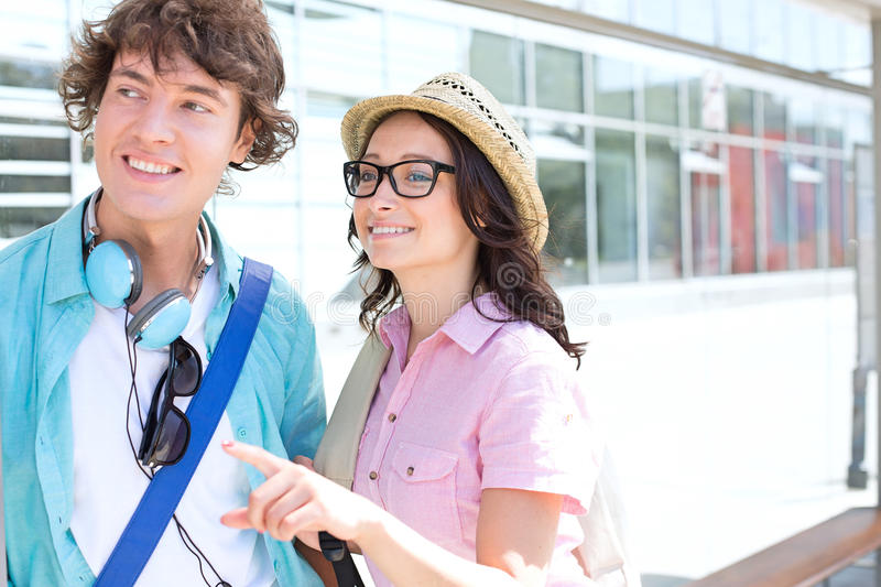 Smiling woman showing something to man while waiting at bus stop royalty free stock photo