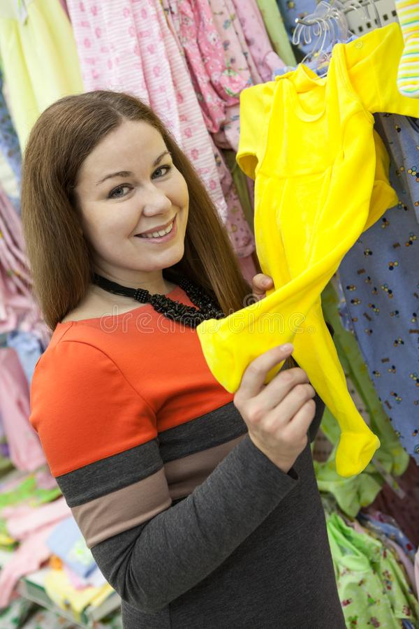Smiling woman showing yellow crawlers for baby while buying clothes in children store. Portrait royalty free stock photo