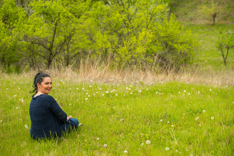 Smiling woman sits in spring grass. Smiling woman take a rest and sitting on spring grass with dandelions stock images