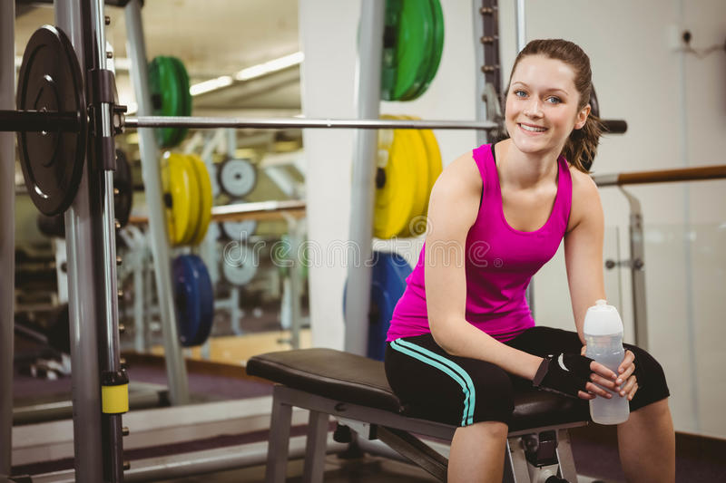 Smiling woman sitting on barbell bench royalty free stock image