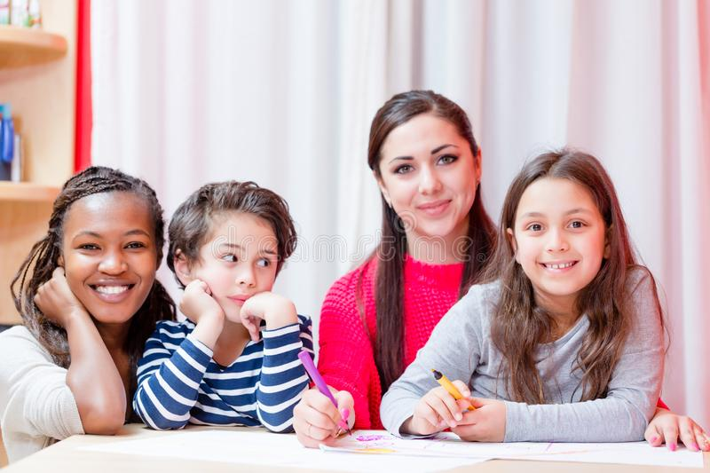 Smiling woman sitting with children royalty free stock photography